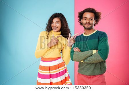 Happy african american young woman pointing on her boyfriend standing with arms crossed over colorful background