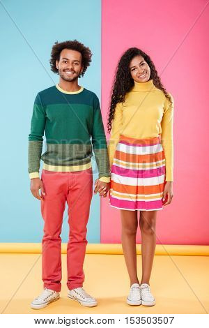 Full length of happy african american young couple standing and holding hands over bright colorful background