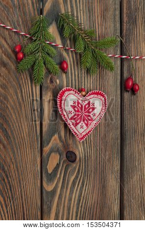 Christmas heart hanging over wooden background.