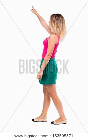 back view of pointing walking  woman. going girl pointing.  backside view of person.  Rear view people collection. Isolated over white background. Girl in a green skirt is showing thumb up.