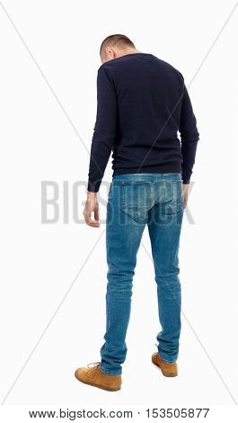 Back view of man in jeans. Standing young guy. Rear view people collection.  backside view of person.  Isolated over white background.  Man in warm jacket looks at his feet.