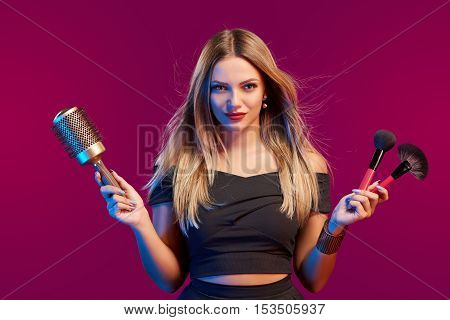 Portrait of female stylist standing with hairdresser's accessories and makeup brushes