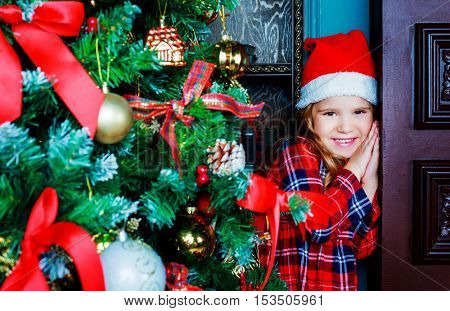 happy cute girl at home hiding behind the Christmas tree