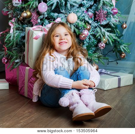 happy girl sitting on the floor at home near her Christmas tree and presents