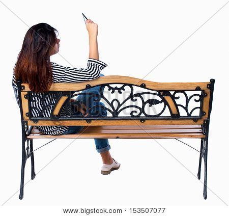 back view of woman sitting on bench and looks at the screen of the tablet.  Rear view people collection. backside view of person. Isolated over white background. Brunette photographed sitting on bench