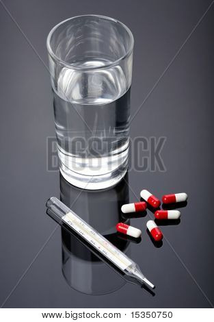 Pills, thermometer and glass of water over dark background