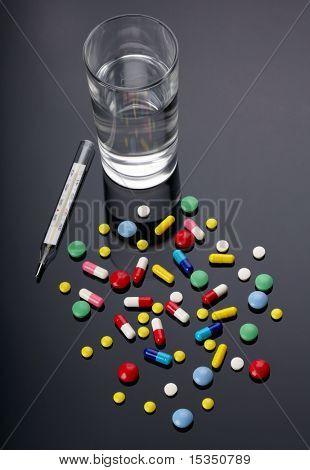 Pillen, Thermometer und Glas Wasser über dunklem Hintergrund