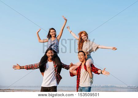 Two happy young women sitting on shoulders of their boyfriends and having fun outdoors