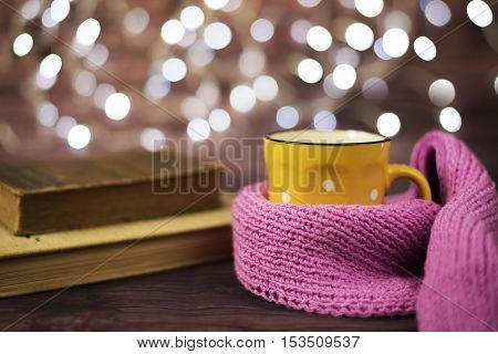 Hot Tea, Hot Chocolate, Coffee In Yellow Cup, Wrapped With A Pink Knitted Scarf.  Old Books. Blurred