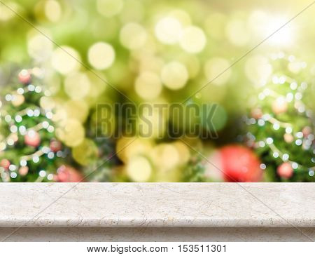 Marble table top with abstract blur christmas tree background with bokeh light. Holiday backdrop. Mock up for display or montage of product.