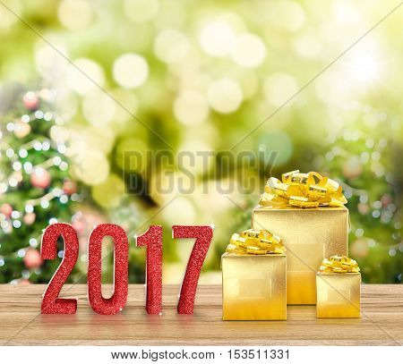 2017 red glitter and Golden present on wood table with christmas tree blurred bokeh light holiday greeting card. 3d rendering