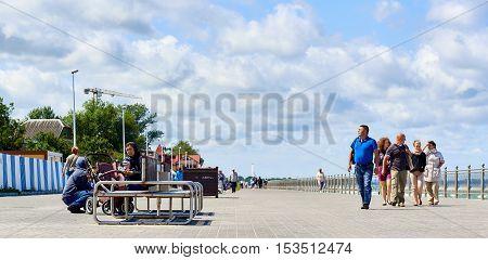 Zelenograd Russia - July 16 2016: People walking along the seafront promenade. Curonian spit Kaliningrad region. Russia