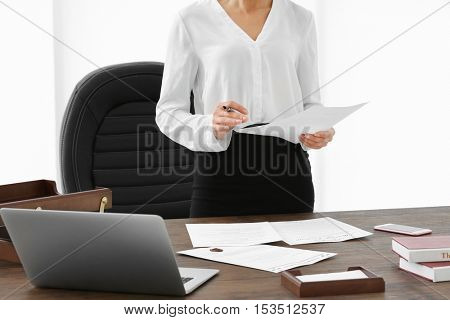 Successful businesswoman working with documents in office, close up view