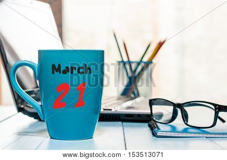 March 21st. Day 21 of month, calendar on business office background, workplace with laptop and glasses. Spring time, empty space for text.