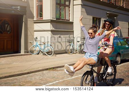 Cute pretty young woman balancing on the handlebars of a bicycle ridden by her friend with her arms and legs outstretched on a sunny summer day