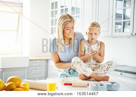 Mother working with child to prepare bread dough ingredients for baking in bright indoor kitchen