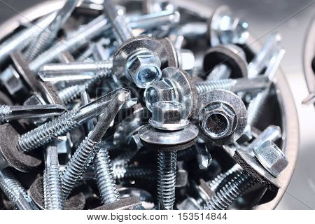 Many screws arranged as background. Metal fasteners piled in a round metal bowl.