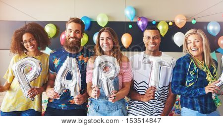Friends holding balloons as letters for PARTY in room with balloons in background