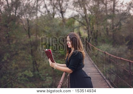 Autumn portrait of a young woman reading a book