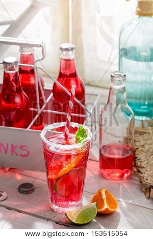 Cold summer drink in bottle on wooden table