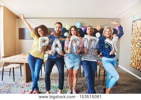 Happy group of young male and female adults holding PARTY letters as they dance in room