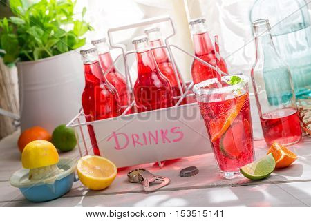 Tasty red orangeade with mint leaf on wooden table