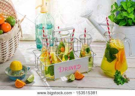 Tasty drink with orange and lemon on wooden table