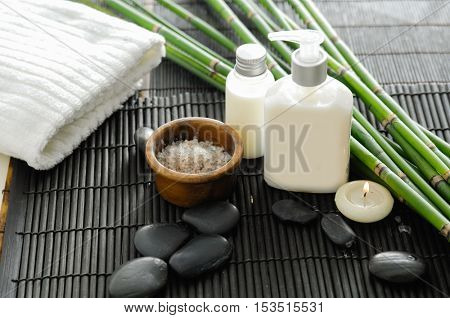 Towel and stones and oil,grove ,Salt in bowl on bamboo mat