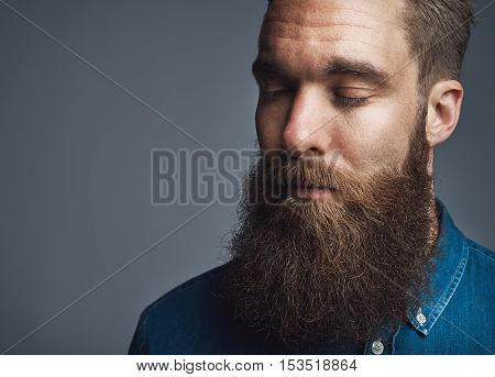 Single calm bearded man in blue denim button shirt and both eyes closed over gray background with copy space