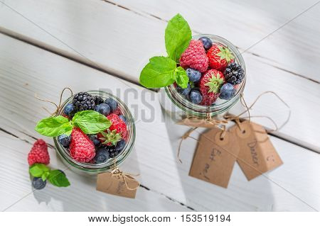 Tasty muesli with fruits and yogurt on wooden table