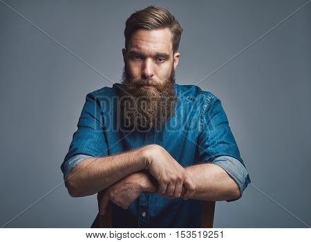 Depressed young bearded man wearing blue denim shirt with rolled up sleeves and arms on back of chair over gray background