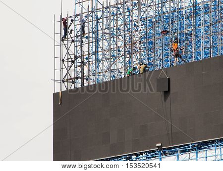 BANGKOK, THAILAND - OCTOBER 24 : Group of workers are climbing poles to install LED billboards. Bangkok, Thailand on October 24 , 2016