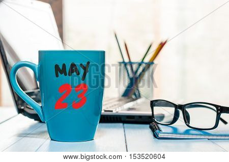 May 23rd. Day 23 of month, calendar on morning coffee cup, business office background, workplace with laptop and glasses. Spring time, empty space for text.