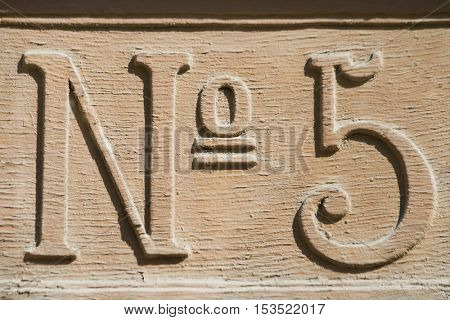 Old street number carved in wood