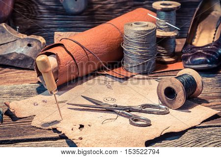 Old Shoemaker Workshop With Tools, Shoes And Laces