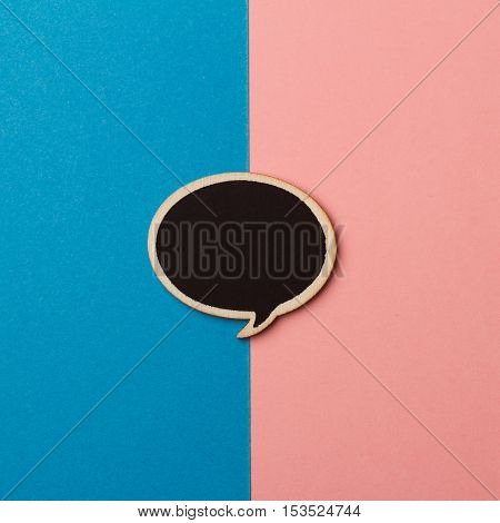 Top view of round empty chalkboard wooden speech bubble on pink and blue background