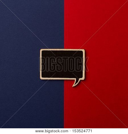 Top view of square empty chalkboard wooden speech bubble on red and dark blue background