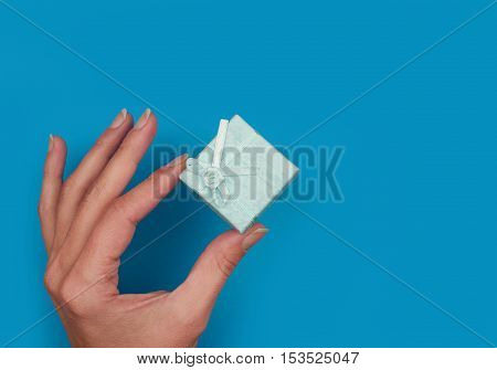 horizontal top view of hand holding with fingers one blue gift box blue background