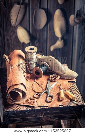 Aged Cobbler Workplace With Shoes, Laces And Tools