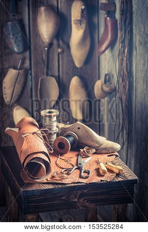 Aged Cobbler Workplace With Tools, Shoes And Leather