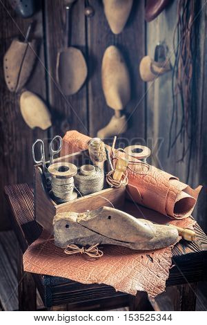 Aged Cobbler Workplace With Tools, Leather And Shoes