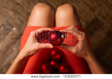 horizontal top view of woman holding Christmas red decoration globes on her lap and one in her hands