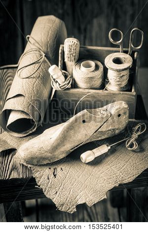 Small Shoemaker Workshop With Tools, Shoes And Laces