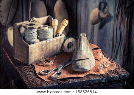 Small Cobbler Workplace With Tools, Leather And Shoes