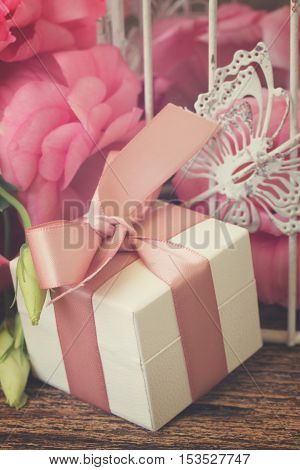 gift box with bow and bunch of fresh roses and eustoma flowers, retro toned