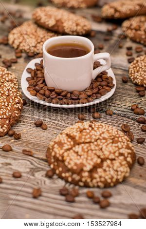 Small white cup of coffee roasted coffee beans cookies with sesame seeds on wooden background