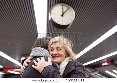 Beautiful senior couple standing at the underground platform, hugging. Welcoming or saying good bye. Five past twelve.