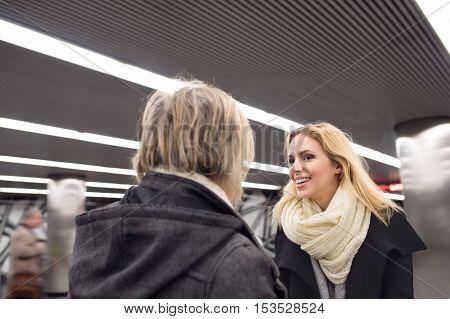 Two beautiful women, mother and daughter, standing at the underground platform, hugging. Welcoming or saying good bye.