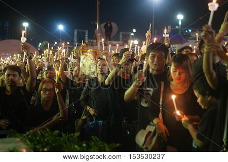 BANGKOK, THAILAND -OCTOBER 22,2016:Thai people singing the anthem and hold the candle for His Majesty King Bhumibol at Sanam Luang at night in front of the Royal Palace to pay respect in Bangkok,Thailand.