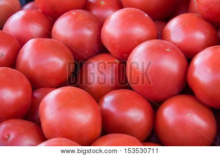 red tomatoes sold on the a market counter.